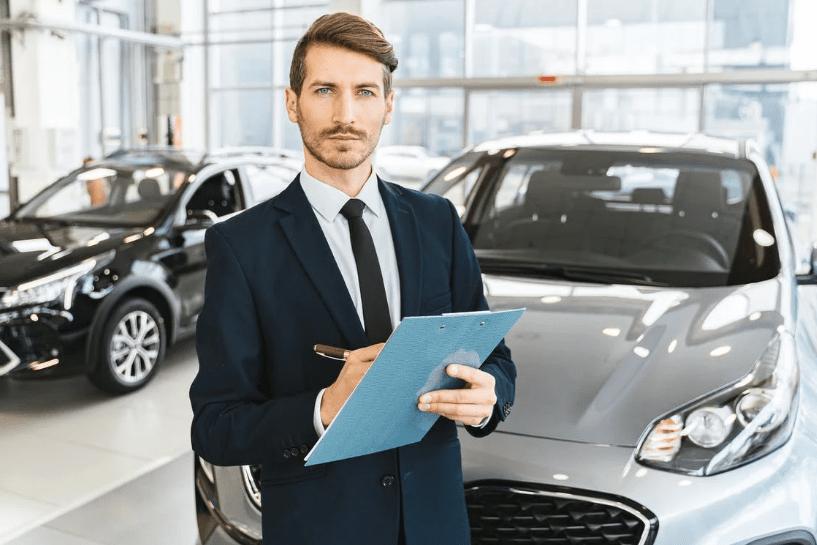 A car salesman holding a blue folder